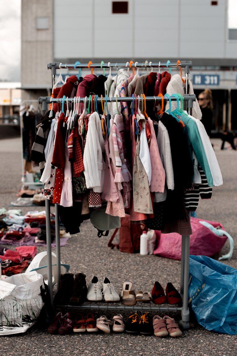 Kirpputorilla oleva vaaterekki, jossa myynnissä olevia vaatteita ja kenkiä