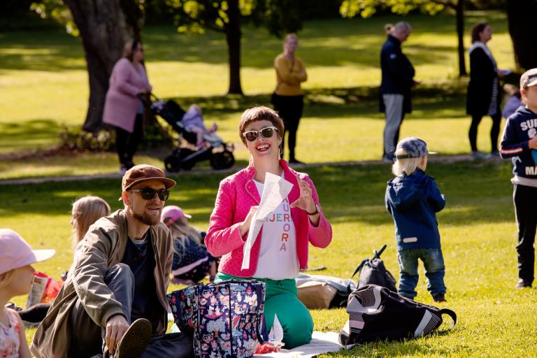 Ihmisiä piknikillä puistossa aurinkoisena kesäpäivänä